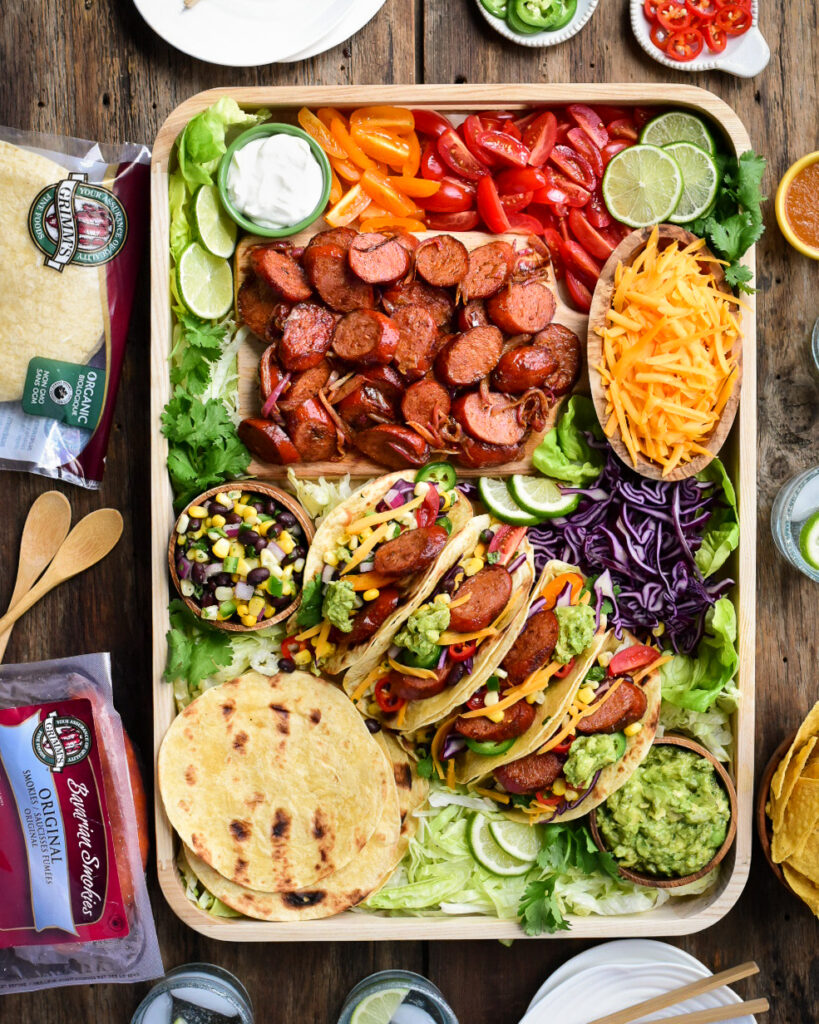 A top down image of a very colourful tray of Bavarian Smokie tacos. Along with the four made up tacos there is a bowl of shredded cheese, a bowl of corn & black bean salsa, a bowl of guacamole, tortillas, sliced grilled sausages, limes, chopped tomatoes and shredded lettuce.