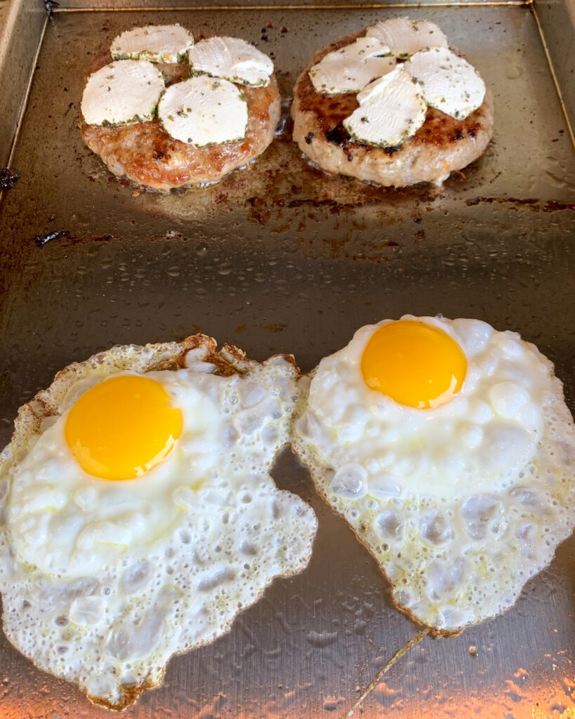 Two turkey burgers with slices of goat cheese on a skillet with two bubbling fried eggs.