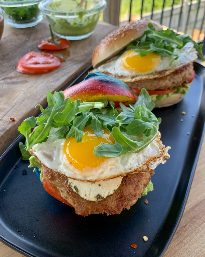 Tow of my GOAT breakfast burger starts with a bagel, a turkey, fennel sausage and goat cheese burger, smashed avocado, sliced tomatoes, more goat cheese, a fried egg and arugula.