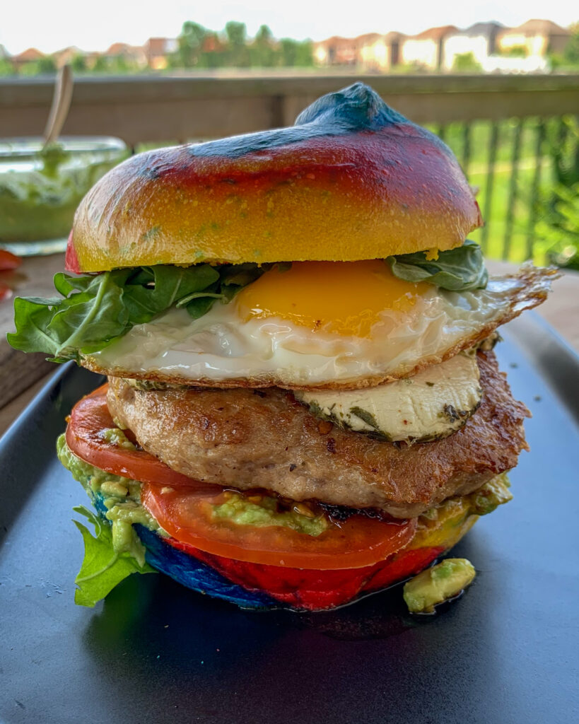My GOAT breakfast burger starts with a bagel, a turkey, fennel sausage and goat cheese burger, smashed avocado, sliced tomatoes, more goat cheese, a fried egg and arugula.