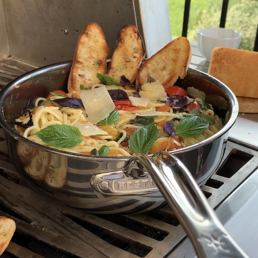 A colourful pan of cherry tomato spaghetti with basil, tomatoes and grilled toast. This dish is being made outside on a grill.