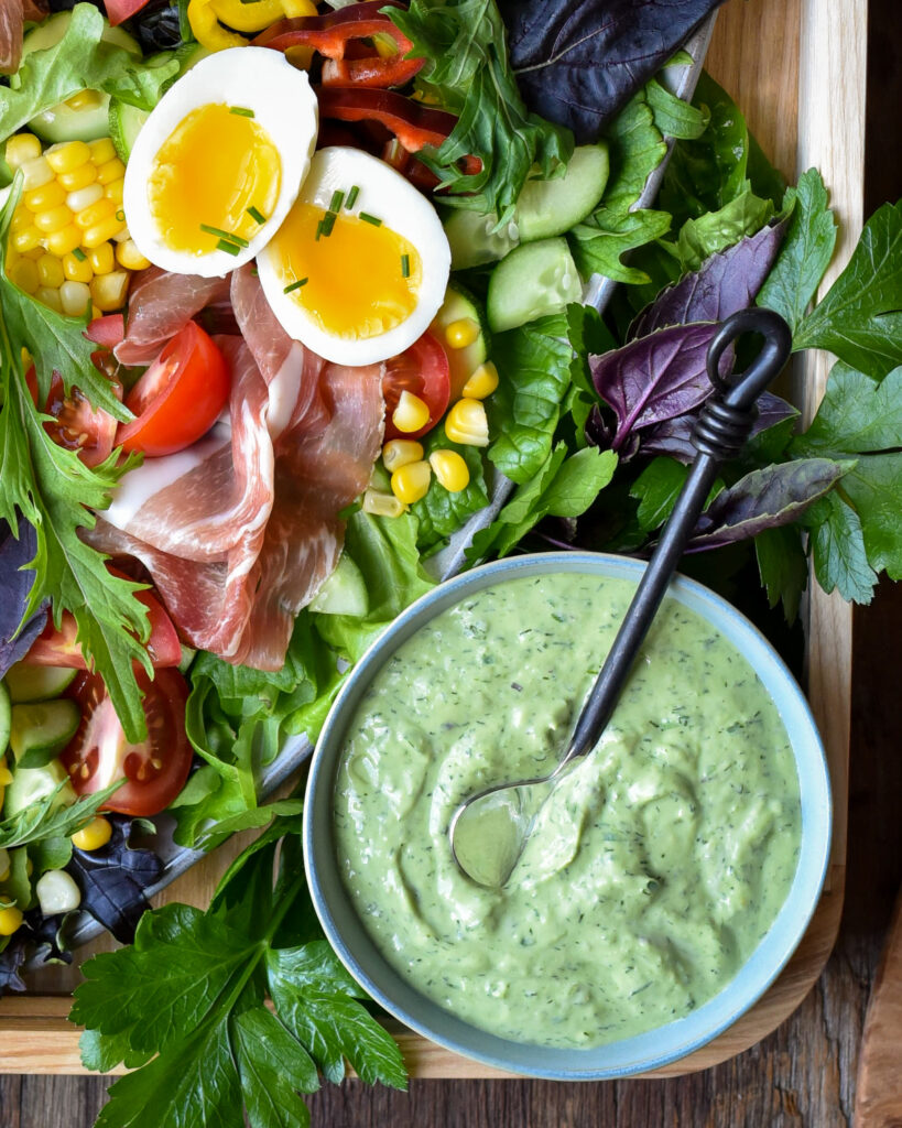 An image of a salad with prosciutto, soft boiled eggs, lettuce, cucumbers and a bowl of green goddess dressing.
