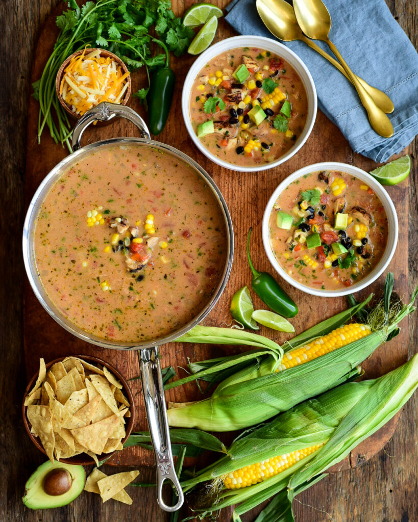 A top down image of corn chowder in a pot and in two separate bowls. Two husks of corn, jalapenos, tortillas, shredded cheese, limes and spoons are all layed out on this table.