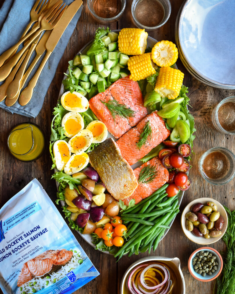 A top down image of a Niçoise inspired salad with wild sockeye salmon. Four pieces of salmon are in the middle of the plate with corn, tomatoes, green beans, potatoes, soft boiled eggs, lettuce and cucumber. Surrounding the plate is a package of the frozen salmon, olives, capers, marinated onions, dressing cutlery, dishes and four glasses of wine.