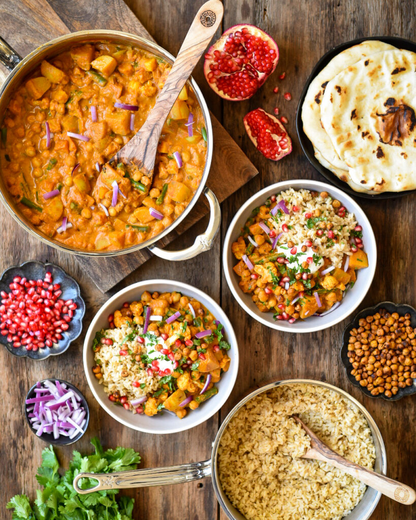 A top down image of Roasted Butternut Squash, Cauliflower and Chickpea Curry. The curry and rice are in separate posts and there are two bowls filled with curry and topped with pomegranate arils, chickpeas, onions and cilantro as well as naan bread.