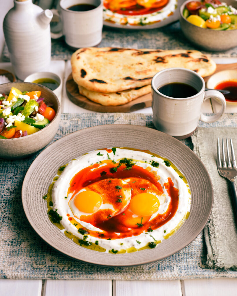 An image of a dish of çılbır eggs. These Turkish inspired eggs are sunny side up on a bed of yogurt and melted butter.  This dish is served with a tomato salad, coffee and naan bread.